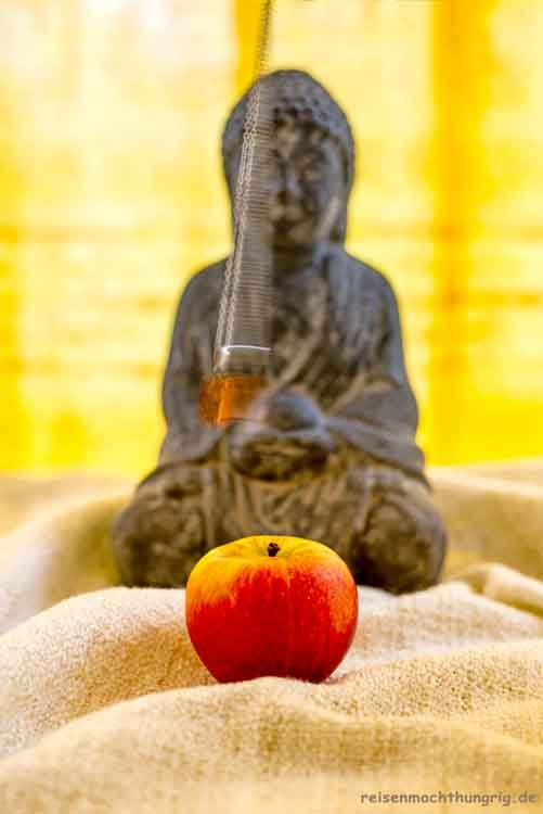 Ernährungsinfos - Buddahfigur mit Pendel und Apfel