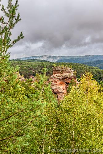 Wandern im Pfälzer Wald mit Felsen und näherkommender Regenwand